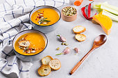Seasonal fall autumn roasted orange pumpkin carrot soup with ingredients on a table.