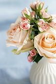 Bouquet of pale pink roses in a vase on blue linen background. . Beautiful Holiday background.