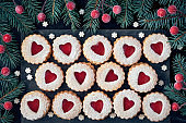 Top view of traditional Christmas Linzer cookies with red jam on dark background decorated with fir twigs and berries