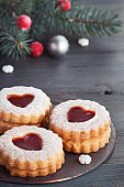 Close-up on traditional Christmas Linzer cookies filled with red jam ondark grey with Xmas decorations
