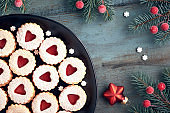 Top view of traditional Christmas Linzer cookies with red jam on rustic wood decorated with berries, srars and snowflakes
