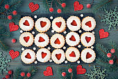 Top view of traditional Christmas Linzer cookies with red jam on rustic wood decorated with berries, hearts and snowflakes