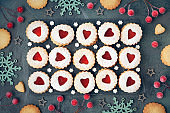 Top view of traditional Christmas Linzer cookies with red jam on dark background
