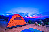 camping with orange tent on hilltop