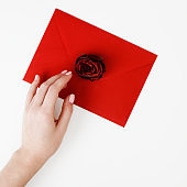 Minimalist fashion and beauty photo. A love letter in a red envelope with a rose. Female hands holding a love letter. The concept of St. Valentine's Day. Romantic photography. 14 february