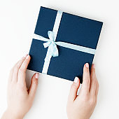 Flat lay. Top view. A minimalistic style of fashion and beauty photography. Hands holding craft paper gift box with as a present for Christmas, new year, valentine day or anniversary