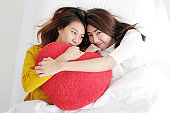 Young cute asia lesbians holding red heart shape willow together lying and smiling with happiness on white bed, LGBT, couple lesbians, valentine's day concept