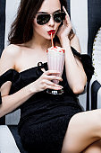 Model young woman beautiful and luxurious sitting with strawberry cocktail in black and white striped chair fashionable and stylish in sunglasses