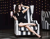 Model young woman beautiful and luxurious sitting with strawberry cocktail in black and white striped chair fashionable and stylish