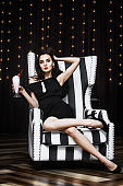 Model young woman beautiful and luxurious sitting in a black and white striped chair fashionable and stylish