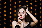 Model young brunette woman beautiful and luxurious portrait on gold lights background