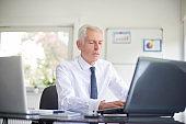 Senior businessman using his laptops