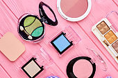 Eyeshadows on pink wooden background.
