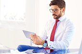 Businessman using digital tablet while working at office desk