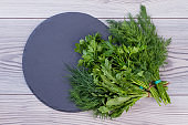 Bunches of fresh herbs on round slate.