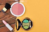 Feminine makeup essentials, color background.