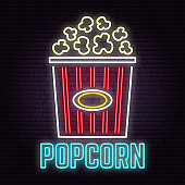 Retro neon popcorn sign on brick wall background.