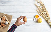 Hand holding brown egg on white wood background