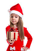 Happy christmas girl looking at the gift holding it in the hand, wearing a santa hat isolated over a white background