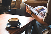 Closeup image of a woman reading a book with coffee cup on wooden table in modern cafe