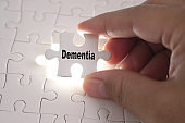 Hands of Professor Doctor holding a jigsaw puzzle with Dementia word. Medical concept.