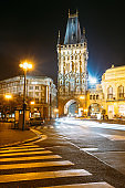 Night View Of The Powder Tower Or Powder Gate. This Landmark Is A Gothic Tower In Prague, Czech Republic