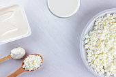 Assorted dairy products on a white board. Cottage cheese, cream and soft cheese on a white background. Milk in a glass, soft cheese for sandwiches. Wooden cutlery. Copy space. Art