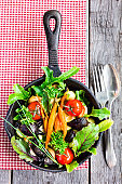 Baked baby carrots, beetroot, cherry tomatoes, pearl onion and garlic in a pan with fresh chard, salad leaves, chive and curly parsley