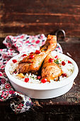 Pair of roasted chicken legs or drumsticks with garlic, served with cooked white rice bowl, pomegranate seeds on a wooden tale, selective focus. Image with copy space. Easter food. Picnic food.