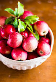 Fresh apples in a bowl on a wooden table, selective focus