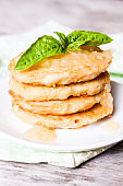 Fried potato cakes or fritters stacked on a plate served with apple sauce and basil leaves, selective focus. Breakfast food, picnic food. Food for Shrove Tuesday.