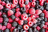 Close up of assorted fresh berries - raspberry and black raspberry, selective focus. Image with copy space. Healthy and organic food option. Vegetarian food. Food background.