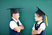 Happy boy and girl in graduation cap in classroom