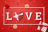 Happy Valentine's Day festive web banner. Top view of the composition with the word love and a realistic gift in the form of a heart, confetti in the shape of a heart and candles on a pink background.