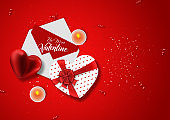 Happy Valentine's Day, web banner. Composition with a realistic gift in the form of heart, paper envelope and candy on a pink background. Romantic background, Flyer, postcard, invitation, top view.