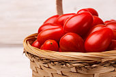 Cherry tomatoes in a basket on a rustic background