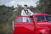Young handsome man with her classic car