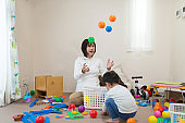 Pregnant mother and toddler playing together with toy in untidy room