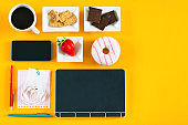 Coffee, breakfast and office accessories on a yellow background