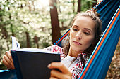 Woman relaxing on hammock and reading a book