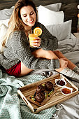 Happy woman eating breakfast in the morning