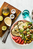 an appetizing dinner or lunch from a salad with tomatoes, grilled eggplants and legume falafel with sesame tahini dressing. Vegan healthy food for the whole family