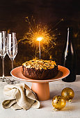 New Year's or Christmas festive chocolate cake with almonds with champagne on the table.