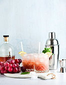 pink alcoholic cocktail of fresh ripe grapes in a shaker with ice, lemon and mint. summer refreshing drink on the table