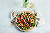 summer, very tasty salad with peaches, sweet onions and arugula with almonds on a table in a plate. simple healthy recipe and a bottle with a glass of white wine