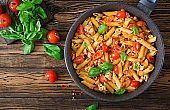 Penne pasta in tomato sauce with chicken, tomatoes, decorated with basil on a wooden table. Italian food. Pasta Bolognese. Top view.
