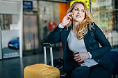 Beautiful businesswoman using phone at the airport and holding passport