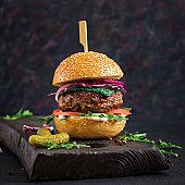 Big sandwich - hamburger burger with beef,  tomato, basil cheese and arugula.