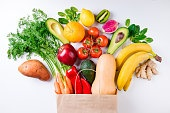 Healthy food background. Healthy food in paper bag fruits and vegetables on white. Vegetarian food. Shopping food supermarket concept