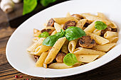Vegetarian Vegetable pasta penne  with mushrooms  in white bowl on wooden table. Vegan food.